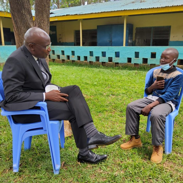 Hon. Wycliffe Wangamati having a chat with Samuel at Nzoia Sugar Primary School.
